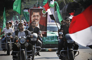 photo -   Palestinian Hamas supporters rally along the streets of Gaza city to support Muslim Brotherhood candidate Mohammed Morsi, Monday, June 18 2012. The Muslim Brotherhood declared early Monday that its candidate, Mohammed Morsi, won Egypt's presidential election, which would be the first victory of an Islamist as head of state in the stunning wave of protests demanding democracy that swept the Middle East the past year. (AP Photo/Adel Hana)