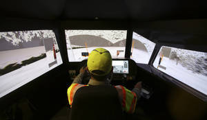 Photo - Driver Terence Mundt operates a snowplow simulator during a North Texas Tollway Authority training class in Plano, Texas, Thursday, Nov. 15, 2012.  The NTTA is using the computer generated simulator to help snowplow operators become better at handling slick roads in a region not used to ice and snow. Highway officials in at least nine states are using the sophisticated simulator to give plow drivers a chance to practice snow removal in any weather. It works like a video game, recreating slick pavement, poor visibility and even children or animals bolting across the road.(AP Photo/LM Otero)