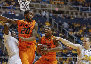 photo - Oklahoma State's Marcus Smart, center, grabs a rebound next to teammate Michael Cobbins (20) and West Virginia's Aaric Murray, left, and Kevin Noreen (34) during the second half of an NCAA college basketball game in Morgantown, W.Va., on Saturday, Feb. 23, 2013. Oklahoma State defeated West Virginia 73-57. (AP Photo/David Smith) ORG XMIT: WVDS110
