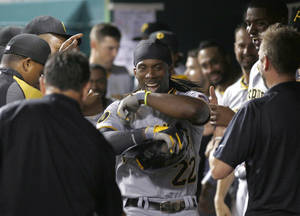 Photo - Pittsburgh Pirates' Andrew McCutchen is congratulated by teammates in the dugout after hitting a solo home run off Cincinnati Reds relief pitcher J.J. Hoover in the 11th inning of a baseball game, Saturday, July 12, 2014, in Cincinnati. The Pirates won 6-5 in 11 innings. (AP Photo/David Kohl)