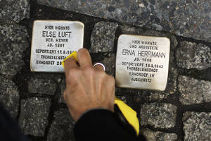 Photo - FILE - In this Nov. 9, 2013 file picture a woman cleans a so called 'Stolperstein', or stumbling stone, set by German artist Gunter Demnig, to remember Nazi victims in Berlin, Germany. The epicenter of the Holocaust, the city where Hitler signed the death warrants of 6 million Jews, seems an unlikely candidate for the world's fastest growing Jewish community. But despite this stigma of Nazism, Berlin's dynamic, prosperous present and its rich, pre-World War II Jewish past initially attracted an influx from the former Soviet Union and has continued with the arrival of thousands of Israelis and smaller numbers of often young immigrants from Australia, France, the United States and elsewhere.   (AP Photo/Markus Schreiber,File)