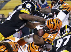 Photo - Cincinnati Bengals running back Gio Bernard (25) gets hit by Pittsburgh Steelers defensive end Ziggy Hood, top left, as he scores a touchdown in the first half of an NFL football game in Pittsburgh, Sunday, Dec. 15, 2013. (AP Photo/Gene J. Puskar)