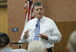 Photo - U.S. Rep. Tom Cole, R-Oklahoma, gestures as he speaks during a town hall meeting in Duncan, Okla, Wednesday, Aug. 28, 2013. (AP Photo/Sue Ogrocki) ORG XMIT: OKSO102