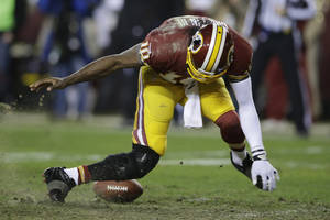 photo - Washington Redskins quarterback Robert Griffin III twists his knees as he reaches for a loose ball after a low snap during the second half of an NFL wild card playoff football game against the Seattle Seahawks in Landover, Md., Sunday, Jan. 6, 2013. (AP Photo/Matt Slocum)