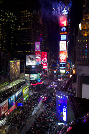 Photo - Looking from the Marriott Marquis hotel, fireworks erupt from One Times Square as the Waterford Crystal ball that will mark the new year is raised into position at six hours before midnight for New Year's Eve celebrations in New York Tuesday, Dec. 31, 2013. (AP Photo/Craig Ruttle)