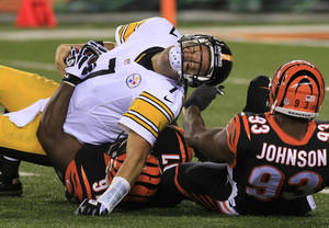Photo - Pittsburgh Steelers quarterback Ben Roethlisberger (7) is sacked by Cincinnati Bengals defensive tackle Geno Atkins (97) and defensive end Michael Johnson (93) in the second half of an NFL football game, Monday, Sept. 16, 2013, in Cincinnati. (AP Photo/Tom Uhlman)