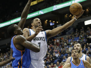 Photo - Minnesota Timberwolves' Derrick Williams, center, lays up a shot as Oklahoma City Thunder's Kendrick Perkins, left, defends and Thabo Sefolosha, right, of Switzerland, watches in the first quarter of an NBA basketball game, Friday, March 29, 2013, in Minneapolis. (AP Photo/Jim Mone) ORG XMIT: MNJM105