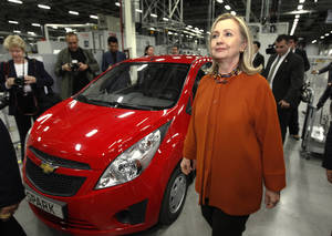 "Photo -   FILE - In this file photo dated Sunday, Oct. 23, 2011, U.S. Secretary of State Hillary Rodham Clinton walks past a General Motors ""Spark"" while touring the GM Powertrain plant in Tashkent, Uzbekistan. Top U.S. officials, including Secretary of State Hillary Rodham Clinton, have paid courtesy calls over the past year, while General Motors and other major U.S. companies look determined to deepen their involvement in the Central Asian nation. The United States is slowly but surely warming to pariah nation Uzbekistan, drawing the former Soviet republic out of its diplomatic wilderness to help with the planned military pullout from Afghanistan. (AP Photo/Kevin Lamarque, Pool,File)"