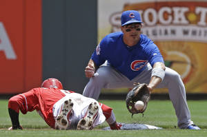 Photo - Cincinnati Reds' Billy Hamilton, left, dives safely back to second base as Chicago Cubs second baseman Darwin Barney catches a pickoff throw in the first inning of a baseball game, Tuesday, July 8, 2014, in Cincinnati. (AP Photo/Al Behrman)