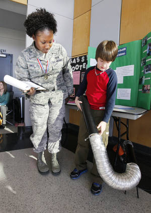 Photo - Fourth-grader Caleb Rice, 10, from Grove Elementary in Shawnee, shows off his snowball maker invention to  Senior Airman Karen Hinds, a contest judge,  during the Oklahoma Student Inventors Exposition held at Rose State College. Photo by Paul B. Southerland, The Oklahoman <strong>PAUL B. SOUTHERLAND - PAUL B. SOUTHERLAND</strong>