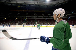 photo - Vancouver Canucks' Cam Barker watches during NHL hockey training camp at Rogers Arena in Vancouver, British Columbia, Monday, Jan., 14, 2013. (AP Photo/The Canadian Press, Jonathan Hayward)