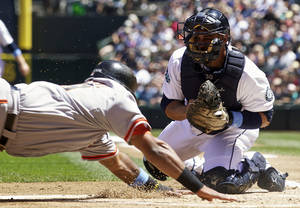 Photo -   Seattle Mariners catcher Miguel Olivo, right, attempts to tag out San Francisco Giants baserunner Pablo Sandoval at home plate during the first inning of a baseball game at Safeco Field in Seattle, Sunday June 17, 2012. Sandoval scored on the play. (AP Photo/Stephen Brashear)