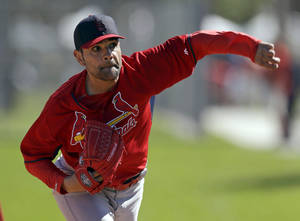 Photo - FILE - In this Feb. 16, 2014 file photo, St. Louis Cardinals pitcher Jaime Garcia throws a bullpen session during spring training baseball practice in Jupiter, Fla. The Cardinals have announced Garcia will return to St. Louis on Sunday to have doctors examine his surgically repaired throwing shoulder, making it unlikely he'll be ready for the start of the season. (AP Photo/Jeff Roberson, File)