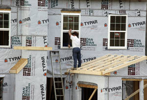 Photo - In this photo made on Friday, March 28, 2014, workers continue construction on a housing plan in Zelienople, Pa. The Commerce Department reports on U.S. home construction in May on Tuesday, June 17, 2014. (AP Photo/Keith Srakocic, File)