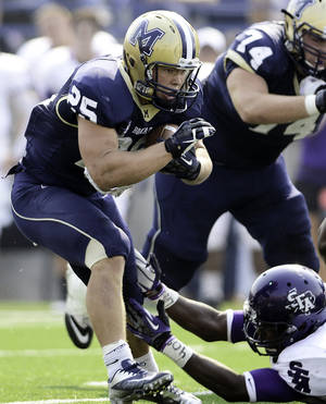 photo -   Montana State running back Cody Kirk (25) fends off a tackle by Stephen F. Austin's Collin Garrett (40) during the first half of their NCAA college football game on Saturday, Sept. 15, 2012, in Bozeman, Mont. Montana State defeated Stephen F. Austin 43-35. (AP Photo/Bozeman Daily Chronicle, Adrian Sanchez-Gonzalez)