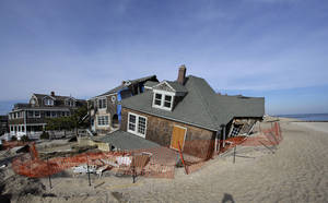 Photo - This Jan. 3, 2013 photo shows a beach front home that was severely damaged by Superstorm Sandy resting in the sand in Bay Head, N.J., Thursday, Jan. 3, 2013.  House conservatives opposed to more deficit spending chip away at a $50.7 billion Superstorm Sandy aid package by seeking spending cuts in other programs to pay for recovery efforts and stripping money for projects they say are unrelated to the Oct. 29 storm.   (AP Photo/Mel Evans)
