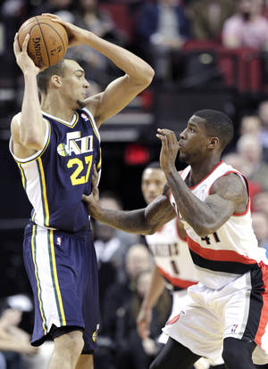 Photo - Utah Jazz center Rudy Gobert, left, maneuvers against Portland Trail Blazers forward Thomas Robinson during the first half of an NBA basketball game in Portland, Ore., Friday, Feb. 21, 2014. (AP Photo/Don Ryan)