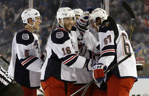 Photo - New York Rangers left wing Benoit Pouliot (67) celebrates wtith teammates after scoring a goal in the second period of an outdoor NHL hockey game against the New York Islanders at Yankee Stadium in New York, Wednesday, Jan. 29, 2014.  (AP Photo/Kathy Willens)