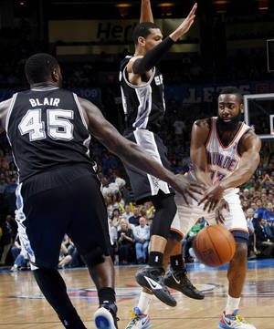 Photo - Oklahoma City's James Harden (13) passes the ball between San Antonio's Danny Green (4) and DeJuan Blair (45) during the NBA basketball game between the Oklahoma City Thunder and the San Antonio Spurs at Chesapeake Energy Arena in Oklahoma City, Friday, March 16, 2012. Photo by Nate Billings, The Oklahoman