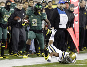 Photo - Oregon running back Byron Marshall, left, evades UCLA defender Anthony Jefferson as he heads down the sideline during the second half of an NCAA college football game in Eugene, Ore., Saturday, Oct. 26, 2013. Marshall ran for 133 yards and three touchdowns for a 42-14 victory. (AP Photo/Don Ryan)