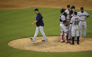 Photo - Cleveland Indians manager Terry Francona, left, walks back to the dugout after making a pitching change during the eighth inning of a baseball game against the Kansas City Royals, Friday, July 25, 2014, in Kansas City, Mo. (AP Photo/Charlie Riedel)