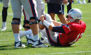 Photo - New England Patriots quarterback Tom Brady  grabs his left knee after an apparent injury during a joint workout with the Tampa Bay Buccaneers at NFL football training camp, in Foxborough, Mass., Wednesday, Aug. 14, 2013. (AP Photo/Will DiTullio)