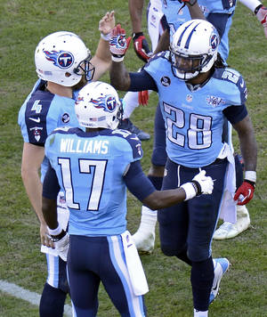 Photo - Tennessee Titans running back Chris Johnson (28) is congratulated by quarterback Ryan Fitzpatrick (4) and wide receiver Damian Williams (17) after Johnson scored a touchdown on an 11-yard run against the Houston Texans in the third quarter of an NFL football game Sunday, Dec. 29, 2013, in Nashville, Tenn. (AP Photo/Mark Zaleski)