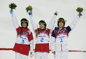 Photo - Canada's Justine Dufour-Lapointe, center, celebrates her gold medal in the women's moguls final, with her sister and silver medalist Chloe Dufour-Lapointe, left, and bronze medalist United States' Hannah Kearney, at the Rosa Khutor Extreme Park, at the 2014 Winter Olympics, Saturday, Feb. 8, 2014, in Krasnaya Polyana, Russia.  (AP Photo/Andy Wong)