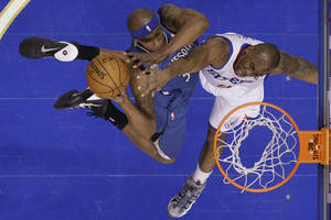 Photo - Minnesota Timberwolves' Dante Cunningham, left, goes up for a shot against Philadelphia 76ers' James Anderson during the first half of an NBA basketball game, Monday, Jan. 6, 2014, in Philadelphia. (AP Photo/Matt Slocum)