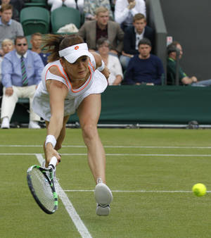 Photo - Agnieszka Radwanska of Poland stretches to play a return to Ekaterina Makarova of Russia during their women's singles match at the All England Lawn Tennis Championships in Wimbledon, London, Monday, June 30, 2014. (AP Photo/Sang Tan)