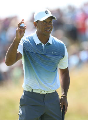 Photo - Tiger Woods of the US holds up his ball after putting out on the 11th green during the first day of the British Open Golf championship at the Royal Liverpool golf club, Hoylake, England, Thursday July 17, 2014. (AP Photo/Peter Morrison)