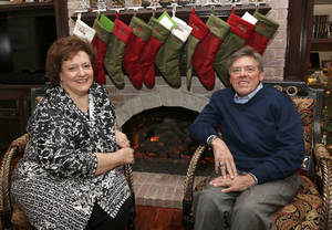 Photo - Phil Busey, founder and CEO of The Busey Group/DRG, and his wife Cathy, sit by the fireplace in their Edmond home.  <strong>PAUL HELLSTERN - Oklahoman</strong>