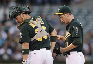Photo -   Oakland Athletics' Jarrod Parker, right, is visited on the mound by catcher Derek Norris, left, in the second inning of a baseball game against the Los Angeles Angels, Monday, Aug. 6, 2012, in Oakland, Calif. (AP Photo/Ben Margot)