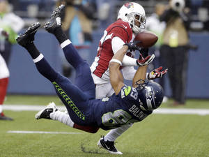 Photo - Arizona Cardinals cornerback Jerraud Powers, top, breaks up a pass intended for Seattle Seahawks wide receiver Doug Baldwin in the second half of an NFL football game, Sunday, Dec. 22, 2013, in Seattle. (AP Photo/Elaine Thompson)