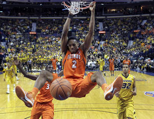 Photo - Illinois' Joseph Bertrand dunks the ball as teammate Brandon Paul and Missouri's Jabari Brown, right, watch during the second half of an NCAA college basketball game Saturday, Dec. 22, 2012, in St. Louis. Missouri won 82-73. (AP Photo/Jeff Roberson)