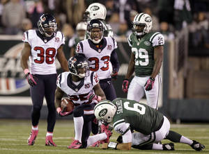 Photo -   In this photo taken Oct. 8, 2012, Houston Texans defensive back Kareem Jackson (25) gets up after returning an interception against New York Jets quarterback Mark Sanchez (6) late in the second half of an NFL football game in East Rutherford, N.J. Jackson interception helped sealed the Texans 23-17 victory. (AP Photo/Kathy Willens)