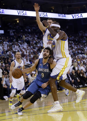 Photo - Minnesota Timberwolves' Ricky Rubio (9) dribbles to the basket as Golden State Warriors' Jermaine O'Neal, right, and Klay Thompson, center, defend during the first half of an NBA basketball game on Monday, April 14, 2014, in Oakland, Calif. (AP Photo/Marcio Jose Sanchez)