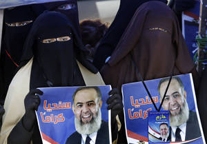 Photo -   FILE - In this Friday, April 20, 2012 file photo, Egyptian women hold posters supporting Muslim cleric Hazem Abu Ismail, an ultraconservative Salafi preacher who was disqualified from running for the presidential elections on technical grounds, during a demonstration at Tahrir Square, in Cairo, Egypt. Radical Islamists in Egypt dream of turning the most populous Arab country into a religious state. With their scourge Hosni Mubarak out of the way, the most extreme fringe of Islamists is flexing its muscles, adding a potentially destabilizing layer to Egypt's multiple political troubles ahead of presidential elections. (AP Photo/Amr Nabil, File)