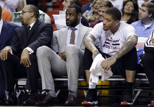 Photo - Miami Heat's LeBron James, center, watches from the bench with teammate Michael Beasley, right, during the first half of an NBA basketball gam against the Chicago Bulls, Sunday, Feb. 23, 2014, in Miami. James is not playing as he is recovering from a broken nose. (AP Photo/Lynne Sladky)