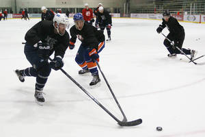 photo -   Winnipeg Jets Andrew Ladd, left, and New York Islanders Travis Hamonic, center, battle for the puck during an informal hockey practice in Winnipeg, Manitoba, on Wednesday, Sept. 19, 2012. The league locked out its players at last weekend, its fourth shutdown since 1992. (AP Photo/The Canadian Press, John Woods)