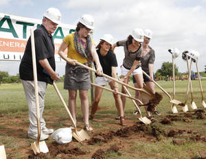 Photo - Edmond swimming Coach Steve Riggs and student swimmers Alyx Siemer, Carlie Pearson, Katie Hettinger and Olivia Stookey take a turn digging at the groundbreaking for the new $22.47 million Edmond Recreation and Aquatics Center. PHOTO BY PAUL HELLSTERN, THE OKLAHOMAN.