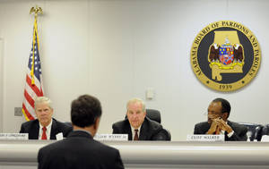 Photo - Robert Longshore, left, William Wynne, Jr. and Cliff Walker listen to Sen. Arthur Orr, R-Decatur, address the Alabama Board of Pardons and Paroles on Thursday, Nov. 21, 2013, in Montgomery, Ala. Three Scottsboro Boys Haywood Patterson, Charlie Weems and Andy Wright, who were falsely accused of having raped two white women in 1937, had their records posthumously cleared. (AP Photo/Montgomery Advertiser, Amanda Sowards)