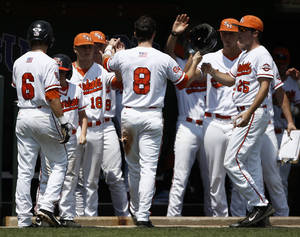 Photo - Sam Houston State's Carter Burgess (8) is congratulated by teammates after scoring on a hit Dylan Ebbs against Siena during an NCAA college baseball regional tournament game in Fort Worth, Texas, Sunday, June 1, 2014. (AP Photo/Jim Cowsert)