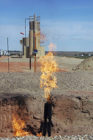 "Photo - FILE - In this Sept. 23, 2008 file photo, natural gas is flared from an oil well near Parshall, N.D. A federal judge has dismissed lawsuits from several North Dakotans who claimed they are owed millions of dollars from oil drilling companies that are burning and wasting natural gas instead of capturing it. U.S. District Judge Daniel Hovland's ruling, filed Wednesday, May 14, 2014, said the federal government lacks jurisdiction in the cases because the mineral owners did not ""exhaust administrative remedies"" with state regulators. (AP Photo/James MacPherson, File)"