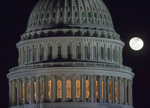 "Photo - The moon rises behind the U.S. Capitol Dome in Washington as Congress works into the late evening, Sunday, Dec. 30, 2012 to resolve the stalemate over the pending ""fiscal cliff."" (AP Photo/J. David Ake)"