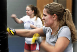 Photo - Roxie Hites works out Tuesday during a kickboxing class  at Huston Huffman on the campus of the University of Oklahoma in Norman.