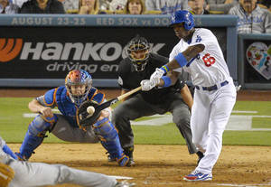 Photo - Los Angeles Dodgers' Yasiel Puig, right, hits a sacrifice fly that scored Adrian Gonzalez  as New York Mets catcher John Buck, left, and home plate umpire Chad Fairchild look on during the sixth inning of their baseball game, Monday, Aug. 12, 2013, in Los Angeles. (AP Photo/Mark J. Terrill)
