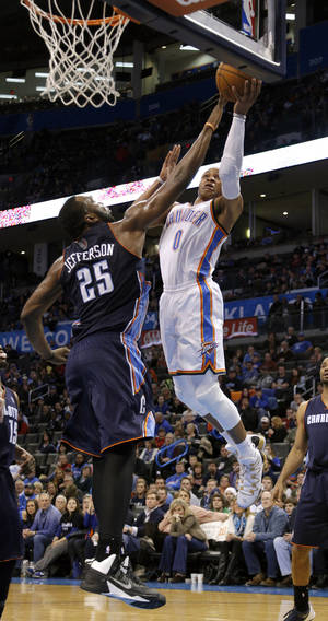 Photo - Oklahoma City's Russell Westbrook (0) goes to the basket as Charlotte Al Jefferson (25) defends during the NBA basketball game between the Oklahoma City Thunder and the Charlotte Bobcats at the Chesapeake Energy Arena, Sunday, March 2, 2014. Photo by Sarah Phipps, The Oklahoman