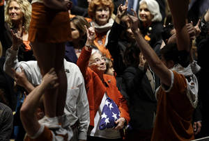 "Photo -   Edith Royal, wife of Darrell K. Royal, center, holds up the Hook'em horns as the ""Eyes of Texas"" is played during a public memorial for her late husband, the former Texas football coach, Tuesday, Nov. 13, 2012, in Austin, Texas. Royal, the coach who led Texas to two national championships and revolutionized college football with the introduction of the wishbone in 1968, died on Nov. 7 at age 88. (AP Photo/Eric Gay)"