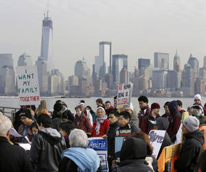 photo - FILE - In this Feb. 13, 2013, file photo, before the New York skyline, a group of immigrant rights advocates gather near Ellis Island in Liberty State Park, Jersey City, N.J. A dispute between business and labor groups over wages for low-skilled workers is a final issue holding up a deal on a sweeping immigration bill in the Senate on Friday, March 22, 2013. (AP Photo/Mel Evans, file)